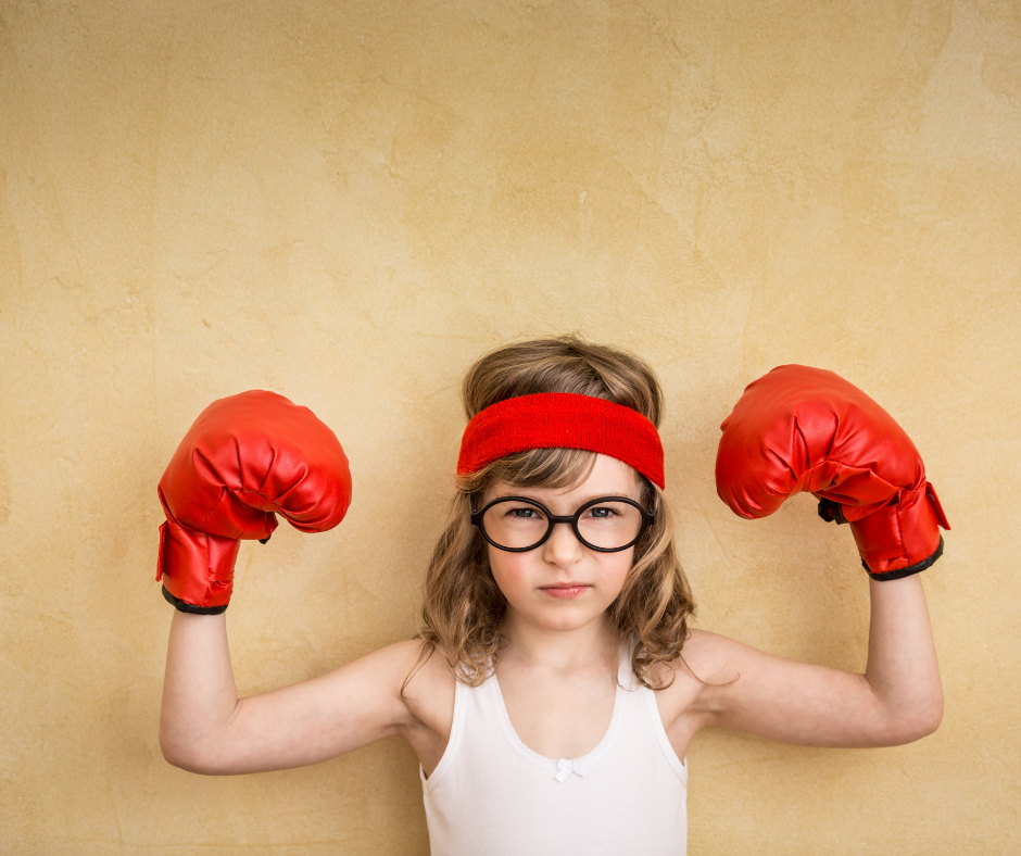 child holding up boxing gloves