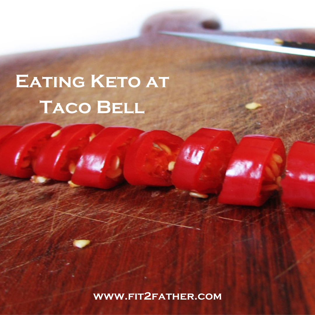 "Red chili peppers cut on a cutting board, with the words ""Eating keto at taco bell"" floating above them"